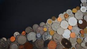 Vista superiore del lotto delle monete dei paesi differenti del mondo disordinato sulla tavola nera Fotografia Stock Libera da Diritti