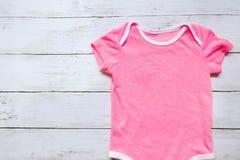 Vista superiore del pagliaccetto rosa del bambino su fondo di legno bianco Copi lo spazio per testo o il grafico fotografia stock