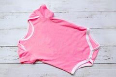 Vista superiore del pagliaccetto rosa del bambino su fondo di legno bianco Copi lo spazio per testo o il grafico Fotografie Stock