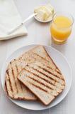 Vista superiore del pane tostato, della spremuta e del burro della prima colazione Immagini Stock