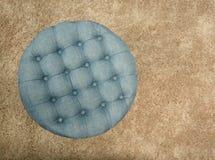 Vista superiore del pouf blu del tessuto rotondo con i bottoni ed i quadrati su tappeto marrone immagine stock
