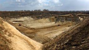 Vista superiore del pozzo di argilla dell'aria aperta con gli escavatori di estrazione mineraria sotto cielo blu Fotografie Stock