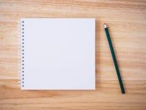 Vista superiore del taccuino bianco della copertura con la matita sullo scrittorio di legno marrone Immagini Stock