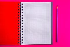 Vista superiore del taccuino in bianco a spirale aperto con la matita sul fondo rosso dello scrittorio immagine stock