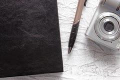 Vista superiore del taccuino e della penna neri vicino alla macchina fotografica della foto sul fondo bianco dello scrittorio per immagini stock libere da diritti