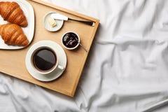 Vista superiore del vassoio di legno con caffè, i croissant, il burro e l'inceppamento su tessuto bianco Prima colazione a letto immagine stock libera da diritti