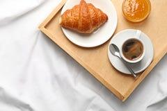 Vista superiore del vassoio di legno con caffè, il croissant e l'inceppamento su tessuto bianco Prima colazione a letto fotografie stock