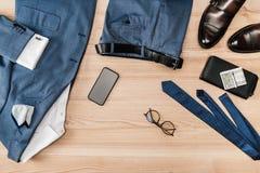 Vista superiore del vestito e degli accessori con lo smartphone Immagine Stock