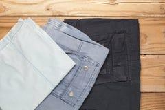 Vista superiore dell'abbigliamento dei pantaloni degli uomini su fondo di legno Fotografie Stock Libere da Diritti