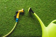 vista superiore dell'annaffiatoio e del tubo su erba, concezione minimalistic immagini stock