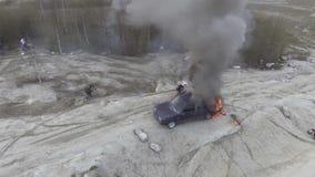Vista superiore dell'automobile bruciante nel giacimento abbandonato della polvere con fumo nero che va su al cielo video d archivio