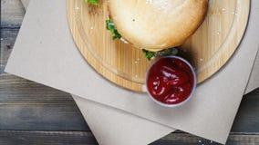 Vista superiore dell'hamburger succoso fresco con formaggio, salsa e le verdure giranti su una tavola di legno stock footage