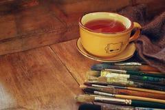Vista superiore dell'insieme dei pennelli usati, della tazza di tè caldo e della tavolozza sopra la tavola di legno Fotografia Stock