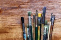 Vista superiore dell'insieme dei pennelli usati sopra la tavola di legno Immagine Stock Libera da Diritti