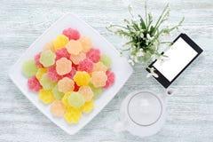 Vista superiore della caramella della frutta da tavola con un telefono, una caffettiera ed i bucaneve freschi sulla tavola di leg Fotografia Stock Libera da Diritti
