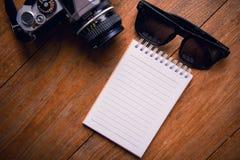 Vista superiore della carta, degli occhiali da sole e delle ukulele del taccuino sull'ufficio de fotografie stock libere da diritti