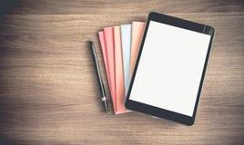 Vista superiore della compressa dello schermo in bianco sulla pila di libro su marrone scuro w immagine stock