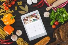 vista superiore della compressa digitale con foursquare il sito Web e gli ingredienti freschi immagine stock libera da diritti