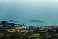 Vista superiore della costa di mare con la foresta, le costruzioni ed acqua blu fotografia stock libera da diritti