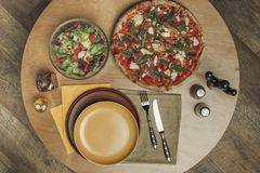 Vista superiore della disposizione dei piatti, della pizza e dell'insalata vuoti Immagine Stock