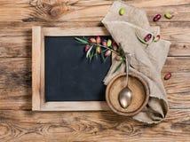 Vista superiore della lavagna del menu sulla tavola con la ciotola, il cucchiaio e il oli fresco Fotografia Stock