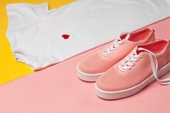 Vista superiore della maglietta della donna bianca e delle scarpe rosa su fondo rosa e giallo Vestiti di modo impostati Disposizi Immagine Stock Libera da Diritti