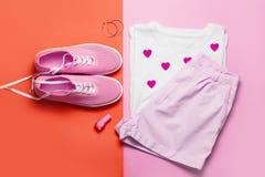 Vista superiore della maglietta della donna bianca e delle scarpe rosa su fondo rosa e rosso Vestiti ed accessori di modo messi D Immagini Stock