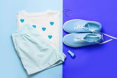 Vista superiore della maglietta della donna e del fondo tonificati blu del blu delle scarpe Fotografia Stock