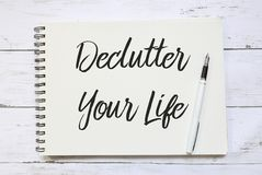 Vista superiore della penna e del taccuino scritti con Declutter la vostra vita su fondo di legno fotografia stock