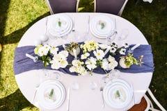 Vista superiore della regolazione della tavola con i fiori bianchi e verdi Fotografie Stock Libere da Diritti