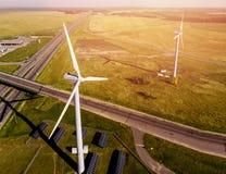 VISTA superiore della strada che passa vicino ai parchi eolici ed ai pannelli solari nel mezzo del campo verde fotografie stock libere da diritti