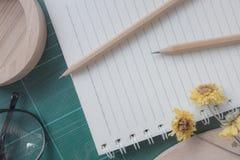 Vista superiore della taglierina di gomma, taccuino, matita, uso ideale per fondo Immagine Stock