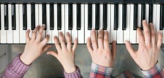 Vista superiore della tastiera di piano e mani del bambino e della madre Fotografia Stock