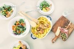 Vista superiore della tavola con il pollo arrostito con il piatto della patata, piatti delle insalate di verdure Fotografia Stock