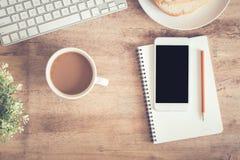 Vista superiore della tavola dell'ufficio Sullo scrittorio abbia lo smartphone e matita del computer portatile della tazza di caf fotografia stock