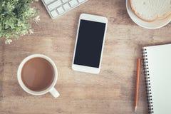 Vista superiore della tavola dell'ufficio Sullo scrittorio abbia lo smartphone e matita del computer portatile della tazza di caf fotografia stock libera da diritti