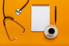 Vista superiore della tavola dello scrittorio di medico con lo stetoscopio, il caffè e la carta in bianco sulla lavagna per appun immagini stock