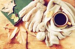 Vista superiore della tazza di caffè nero con le foglie di autunno, una sciarpa calda ed il vecchio libro su fondo di legno immag Fotografia Stock Libera da Diritti
