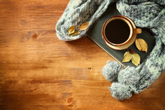 Vista superiore della tazza di caffè nero con le foglie di autunno, una sciarpa calda ed il vecchio libro su fondo di legno immag Fotografia Stock