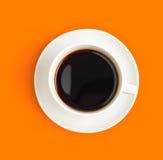 Vista superiore della tazza di caffè nero sull'arancio Fotografie Stock