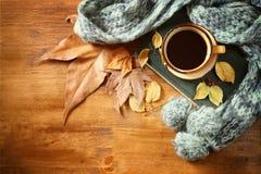 Vista superiore della tazza di caffè nero con le foglie di autunno, una sciarpa calda ed il vecchio libro su fondo di legno immag Immagini Stock