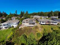 Vista superiore della vicinanza, delle case, degli alberi e del cielo blu suburbani immagine stock