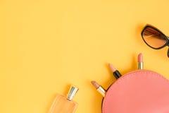 Vista superiore delle borse cosmetiche con i rossetti, vetri, profumo Immagini Stock