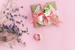 Vista superiore delle fedi nuziali dorate, della busta decorativa e di bei fiori sul rosa Fotografia Stock