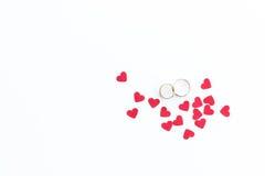 Vista superiore delle fedi nuziali dorate e dei simboli rosa dei cuori isolati su bianco Fotografia Stock