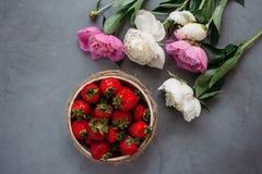 Vista superiore delle fragole in ciotola sul mazzo rosso del fondo delle peonie fotografie stock