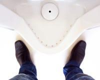 Vista superiore delle gambe di un uomo davanti all'orinale nella toilette degli uomini immagine stock