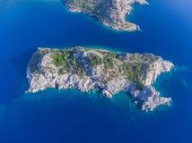 Vista superiore delle isole della roccia in mezzo dell'acqua di mare blu Fotografia Stock