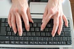Vista superiore delle mani che scrivono su un computer portatile Fotografie Stock Libere da Diritti