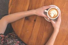 Vista superiore delle mani che tengono una tazza di caffè immagini stock